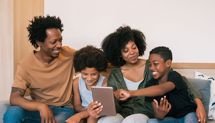 Black family with young children on couch looking at the Sensory Friendly Solutions newsletter on a tablet