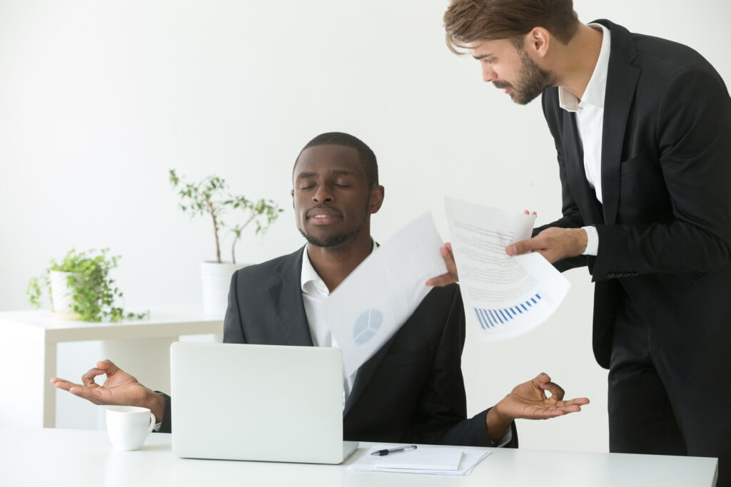 An african american man meditating at his desk at work, practicing mental health for startups, as someone brings him papers to read.