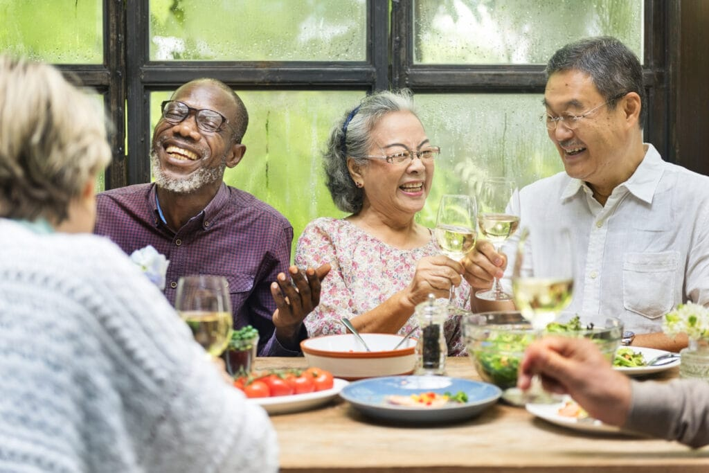 Group of adults at dinner table drinking wine.