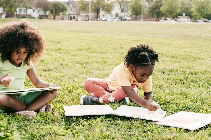 Two girls sitting on grass drawing on paper.