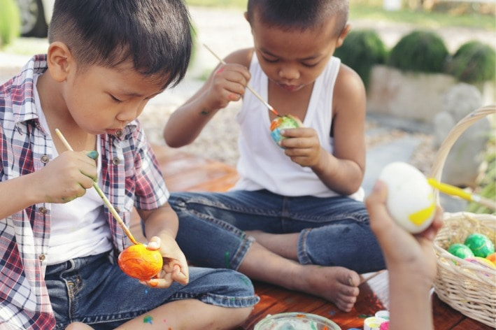 Two young boys sitting on blanket painting Easter Eggs