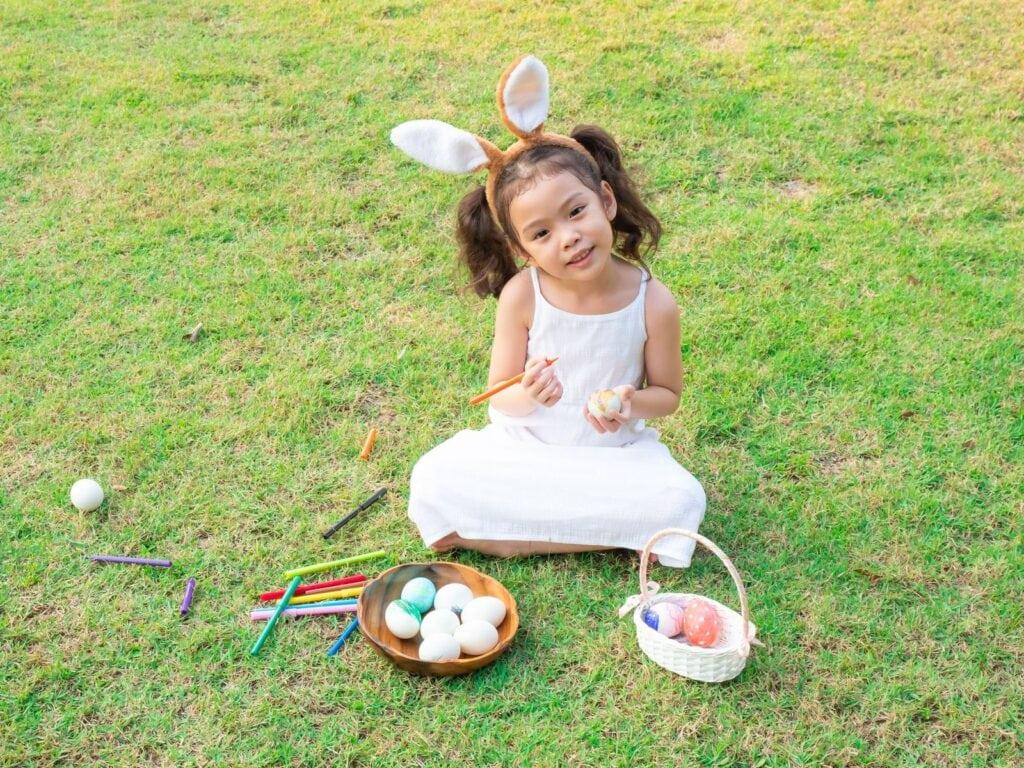Little girl sitting on grass wearing bunny ears