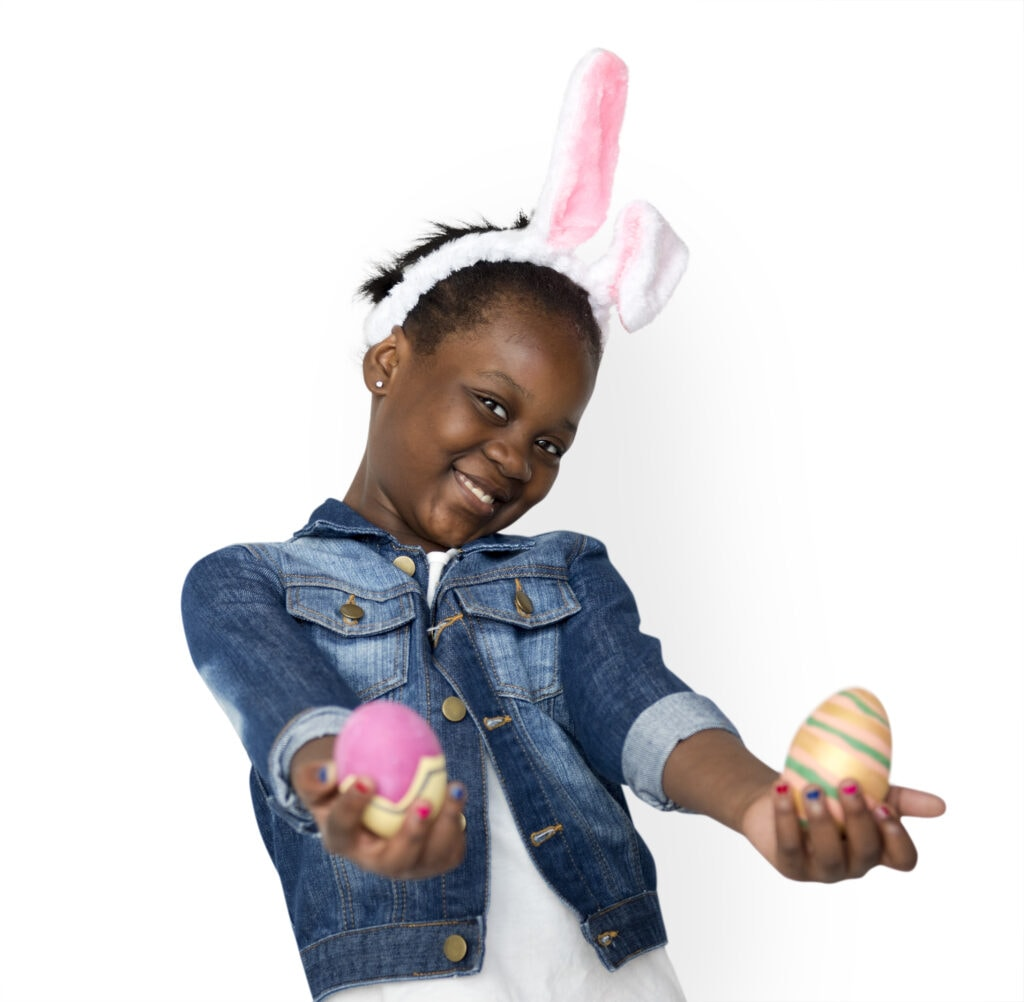 Little girl holding out Easter eggs smiling at camera.
