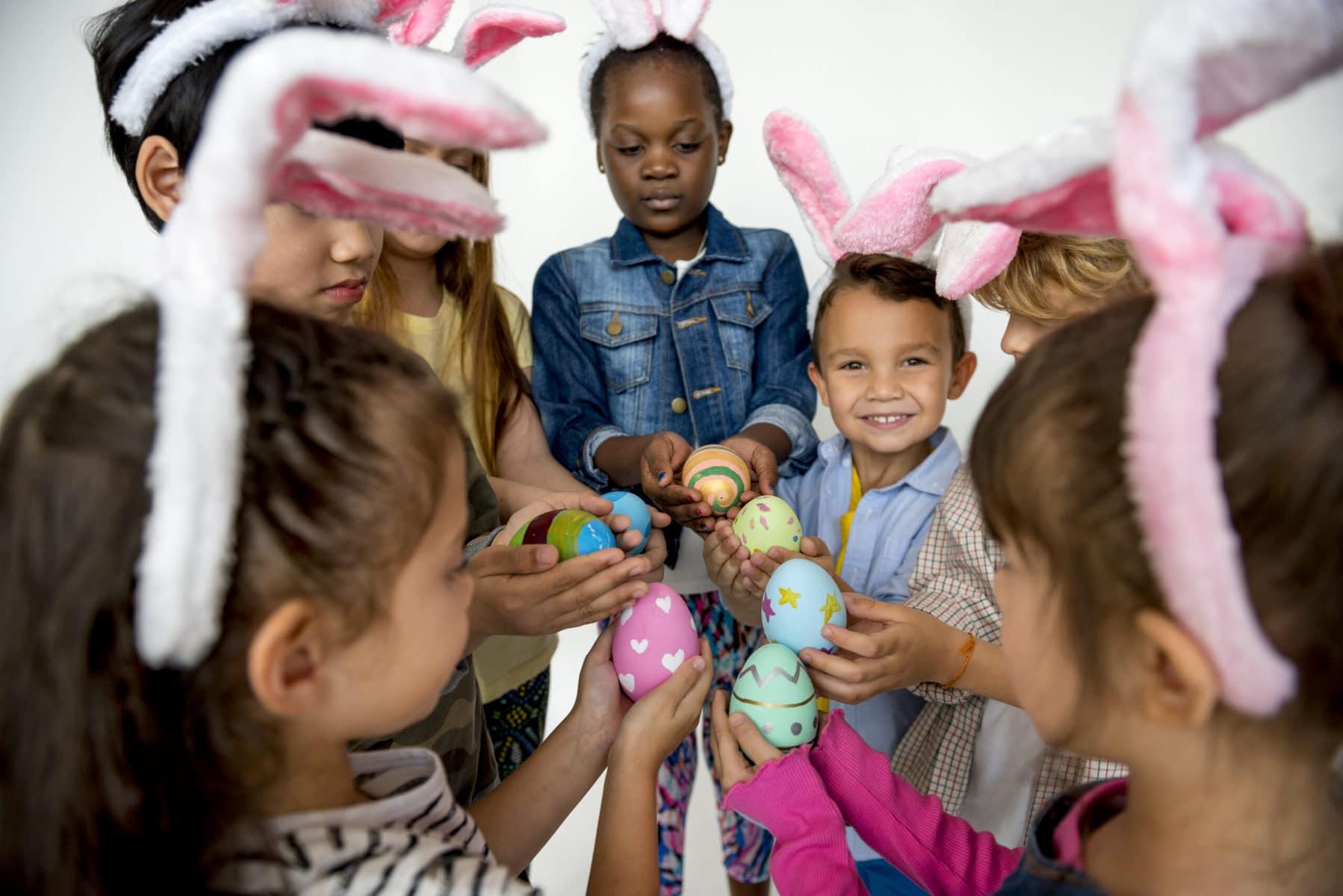 Group of kids on Easter holding Easter eggs.