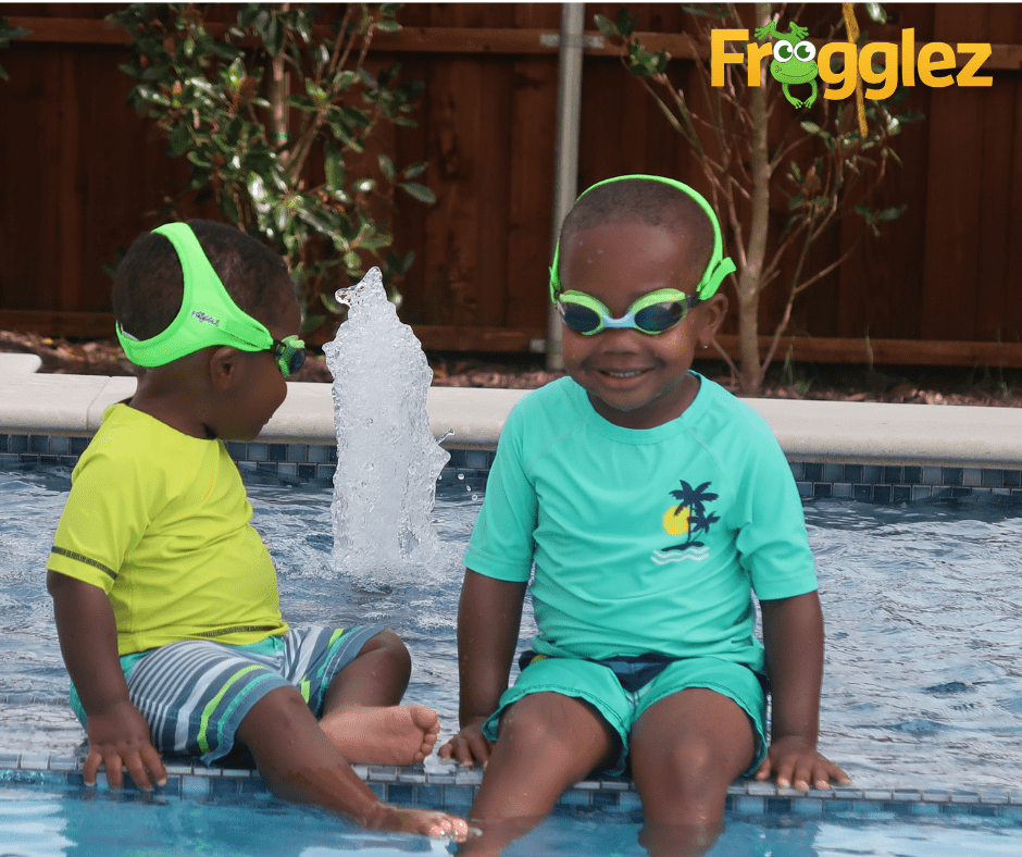 Two young boys sitting in a pool wearing Frogglez goggles, an example of sensory-friendly clothing.