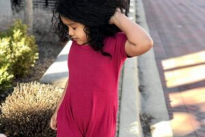 Young girl posing wearing sensory-friendly jumper.