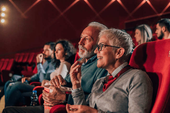 Older adult couple sitting in movie theatre.
