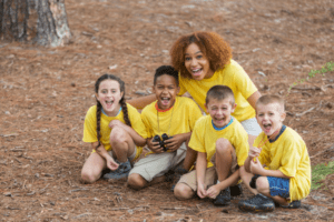 Children and camp counsellor smiling at outdoor camp.