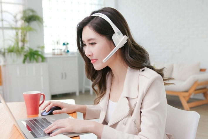 Young asian woman sitting at desk in front of computer wearing a headset.