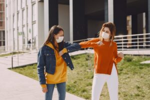 Two women walking wearing masks bumping elbows during COVID..