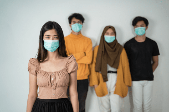 Group of individuals standing distanced wearing masks during the pandemic.