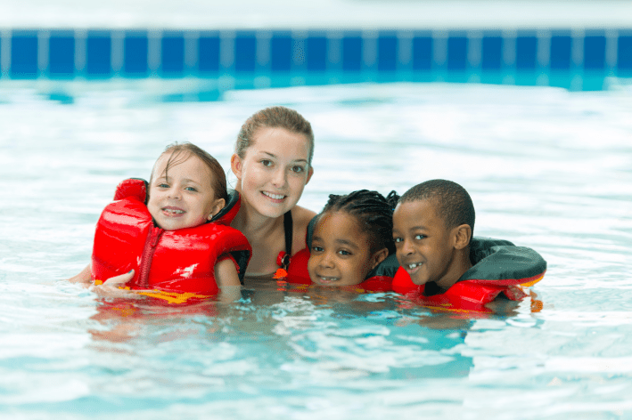Three young children at sensory-friendly swim lessons with a swimming instructor.