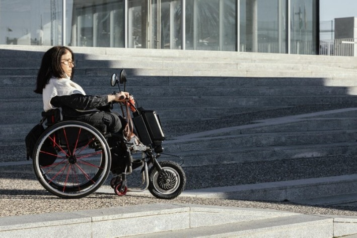 Woman sitting in wheelchair on concrete.