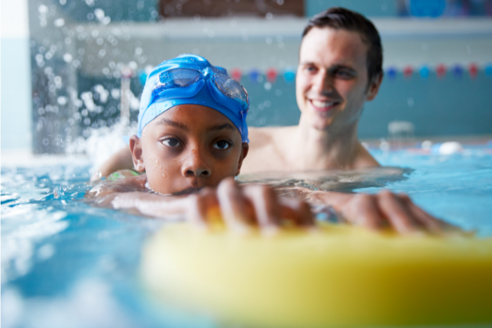 Young boy and swim instructor during sensory-friendly swim lessons.
