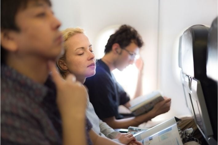 Woman sitting on plane between two passengers experiencing sensory overload.
