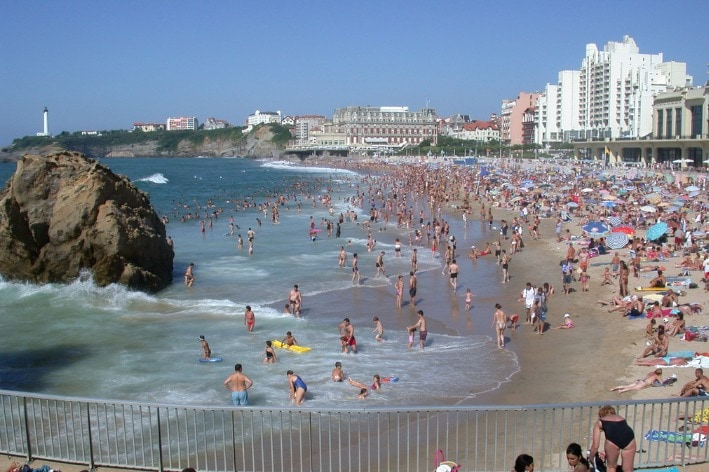 Beach with busy with many different people.