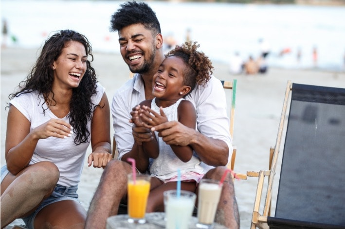 Young couple and child sitting at sensory-friendly beach.