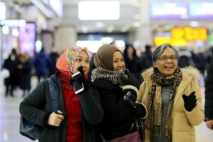 A woman her two daughters standing in a busy airport.