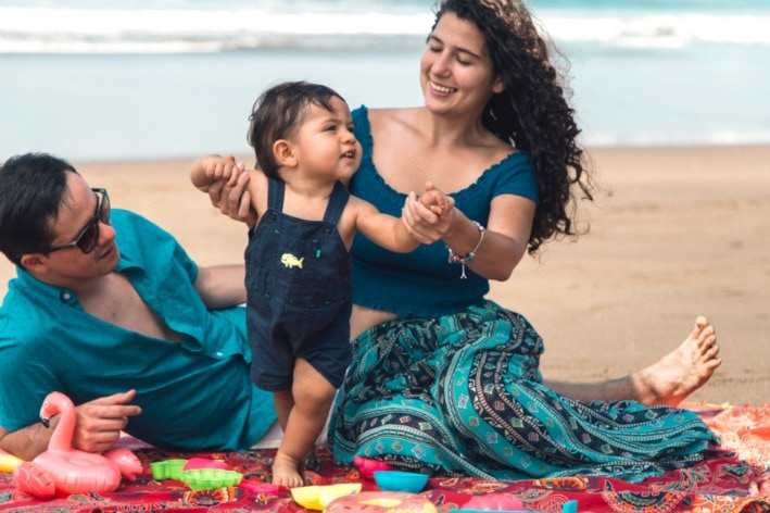 Young family sitting on beach towel at sensory-friendly beach.