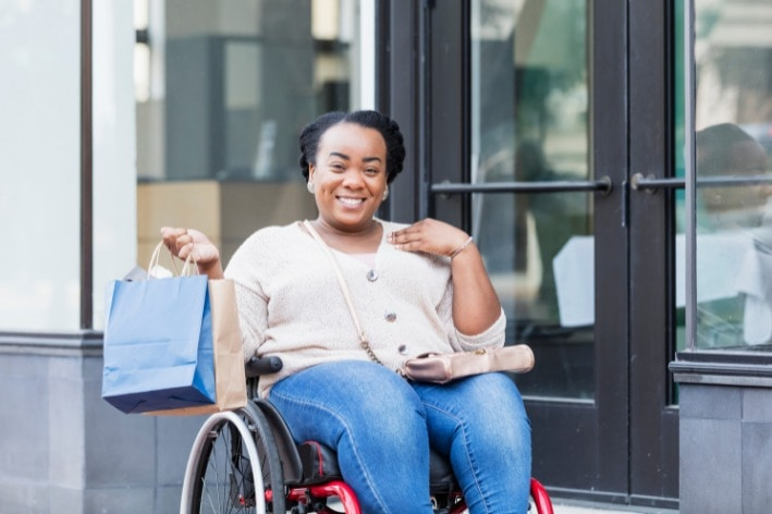 Woman in wheelchair shopping at sensory-friendly business.