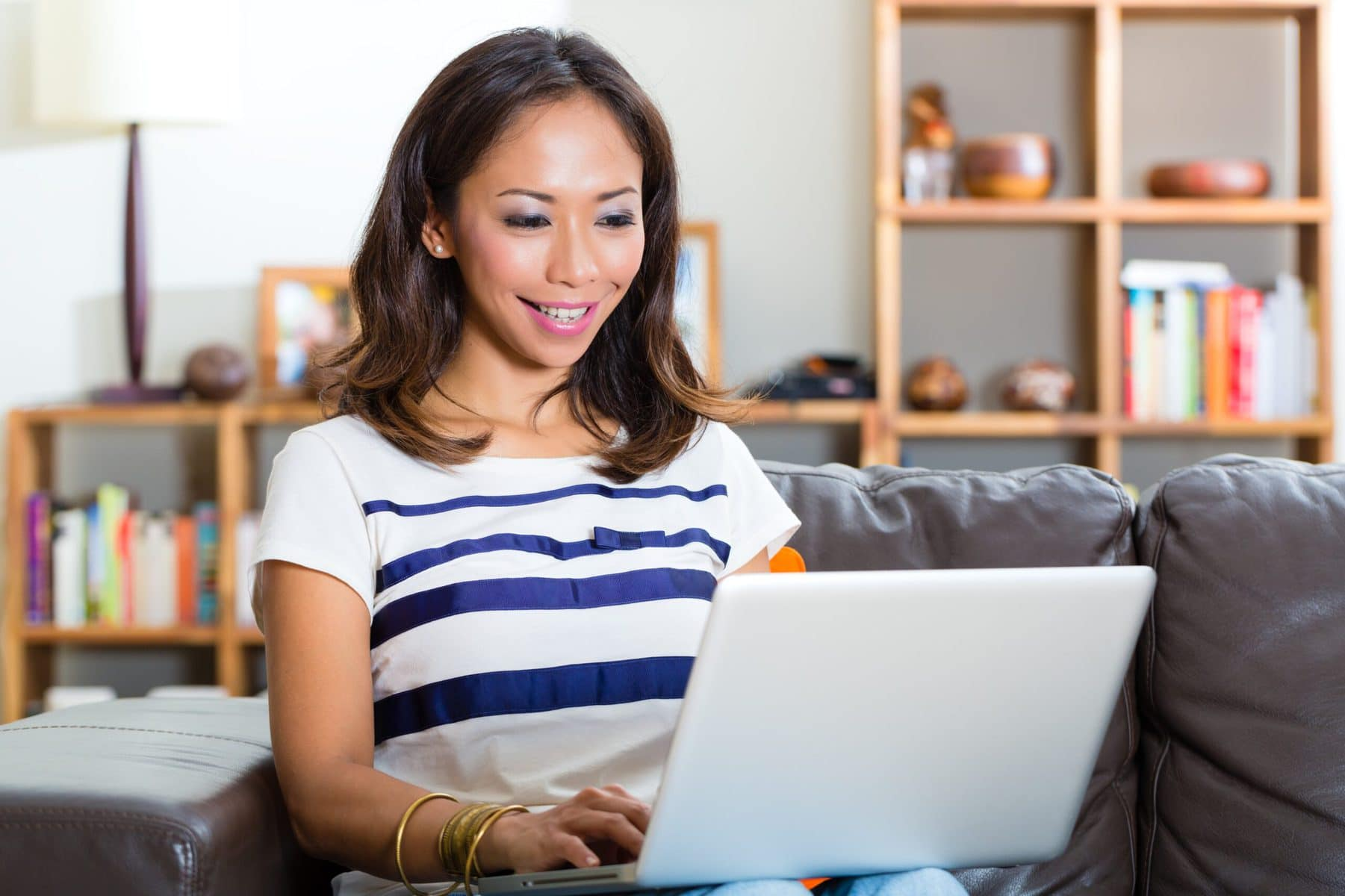Young woman sitting on couch with laptop reading a sensory-friendly email.