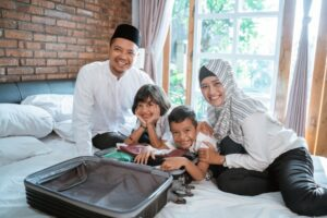 Young family sitting on hotel bed with suitcase while on a sensory-friendly vacation.