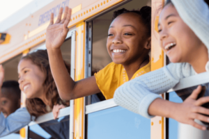Young students smiling waving outside of school bus window.