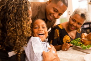 Family smiling at dinner table during sensory-friendly Thanksgiving.