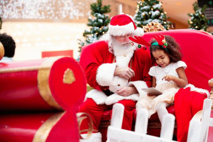 Child sitting beside Sensitive Santa