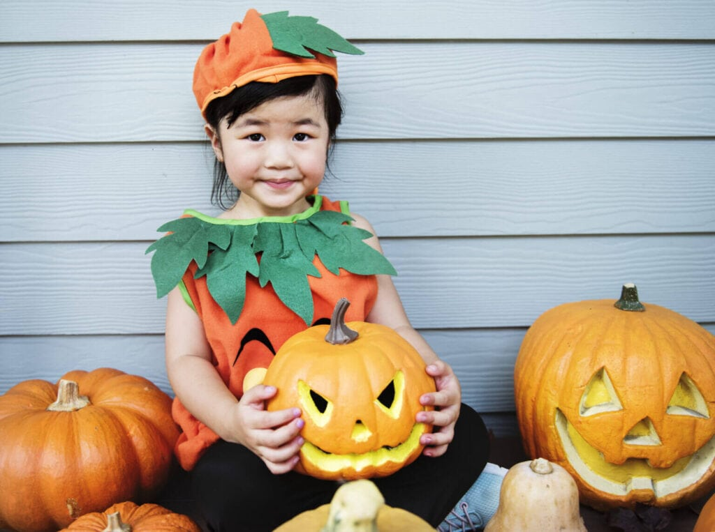 Young girl dressed as a pumpkin for Halloween holding a pumpkin.