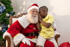 Young boy sitting on Sensitive Santa's lap whispering into his ear.