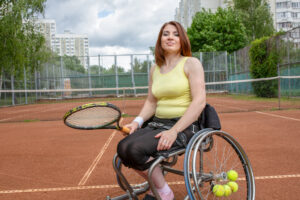 disabled young woman sitting in a wheelchair playing tennis